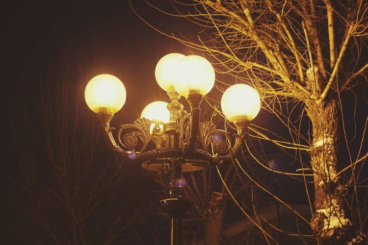 Low angle view of illuminated street light against sky at night