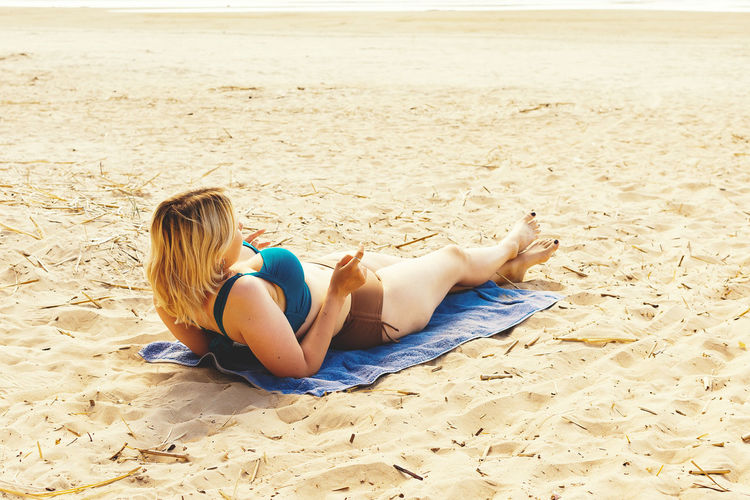 Woman lying down on sand at beach