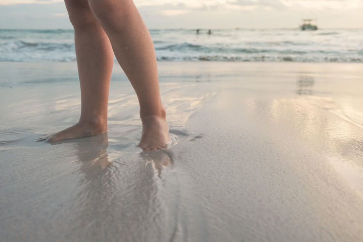 Beach Land Water Sea One Person Leisure Activity Sand Real People Low Section Human Leg Lifestyles Nature barefoot Human Body Part Wet Holiday Day Body Part Outdoors Human Foot Child One Girl Only Sunrise Copy Space Reflection