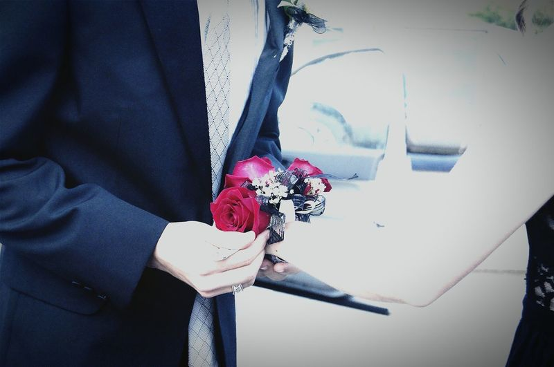 Midsection of man in suit holding roses