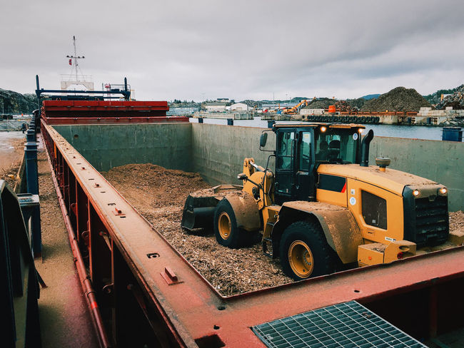 Excavator loading the wood chips into a cargo vessel. Cargo Cargo Hold Cargo Ship Cargo Vessel Cloudy Daytime Excavator Fjords General Cargo Heavy Machinery Hold Industrial Industrial Machinery Machinery Marine Industry Nautical Vessel Norway Outdoors Ship Transportation Vessel Wood Chips