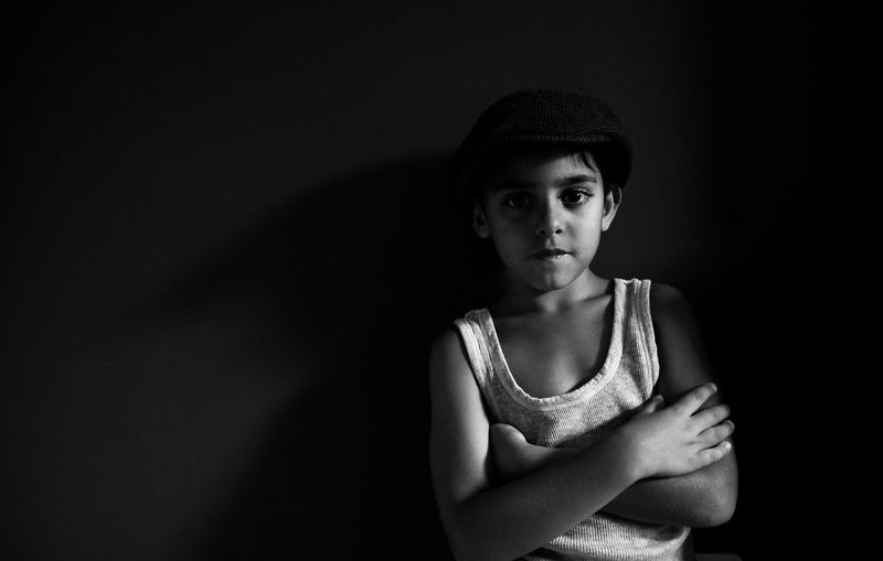 Portrait Looking At Camera Front View One Person Indoors  Studio Shot Black Background Child Waist Up Arms Crossed Casual Clothing Childhood Standing Lifestyles Serious Young Adult Emotion Teenager Dark Contemplation Adolescence  Teenage Boys
