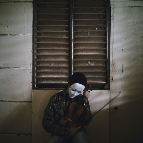 Man wearing mask with violin against window