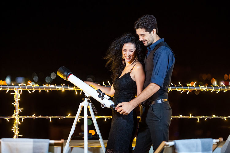 Young Couple With Telescope On Terrace At Night