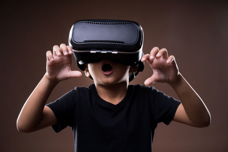Boy using virtual reality simulator while standing against brown background