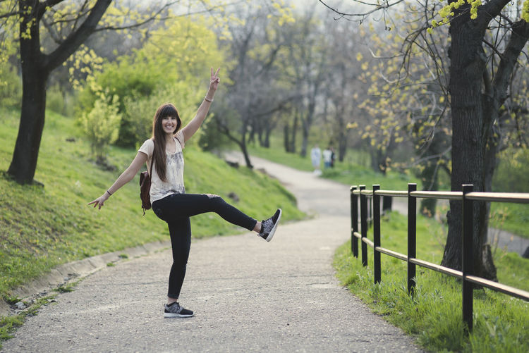 beautiful young woman having fun outside in the girl with long brown hair smiling Adult Arms Raised Casual Clothing Day Focus On Foreground Footpath Front View Full Length Human Arm Leg Leisure Activity Lifestyles Nature One Person Outdoors Plant Real People Tree Women Young Adult Young Women