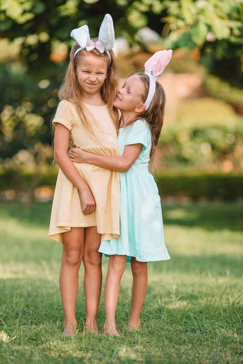 Sisters embracing while standing outdoors