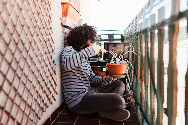 Side view of man holding potted plant while sitting in balcony