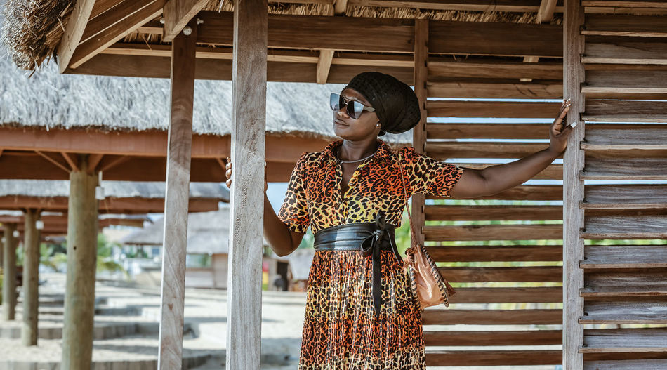 Woman wearing sunglasses standing against built structure