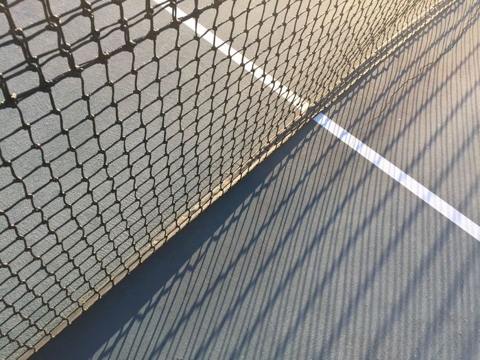 High angle view of net at tennis court during sunny day
