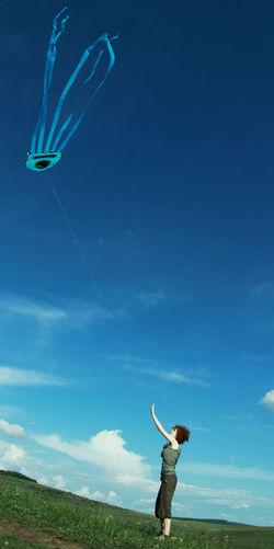 Tilt shot of woman flying kite on field