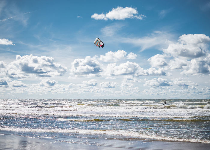 Scenic view of sea against sky with person kiteboarding