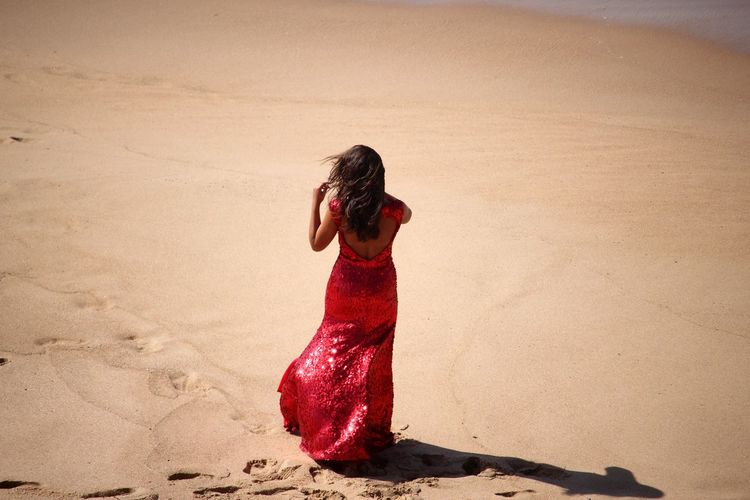 Rear View Of Woman In Red Gown Walking On Sand At Beach