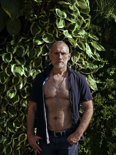 Portrait of a man standing against vertical garden