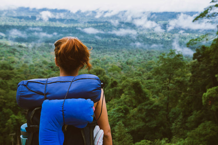 Rear view of woman with backpack standing against forest