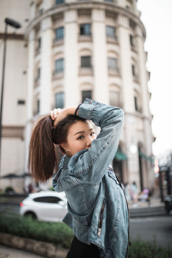 Portrait of young woman tying hair while standing on street in city