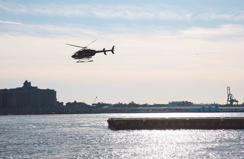 Helicopter flying over river against sky