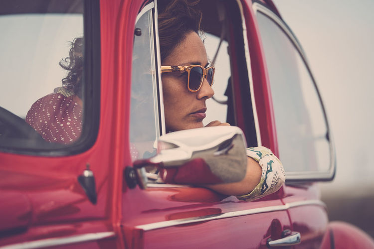 Serious caucasian lady looking outside her car with thoughts - people thinking stressed - insurance concept for women drivers - travel and lifestyle middle age One Woman Only Females Enjoying Life Freedom Red Car Vintage Casual Clothing Caucasian Mode Of Transportation Transportation Land Vehicle Car Real People Young Adult Motor Vehicle One Person Headshot Lifestyles Young Men Portrait Glasses Leisure Activity Travel Adult Red Looking Window Outdoors Young Woman Smiling 40-44 Years Fashion People