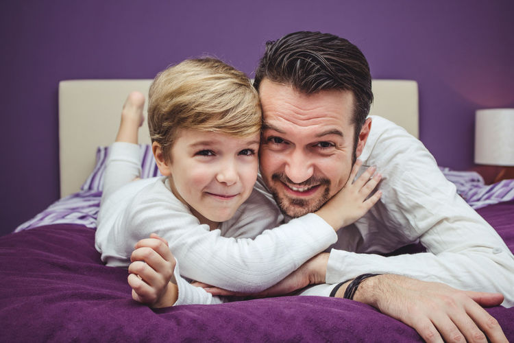 Portrait of father and son lying on bed at home