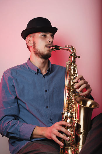 Young Man Wearing Hat Playing Saxophone While Sitting Against Wall