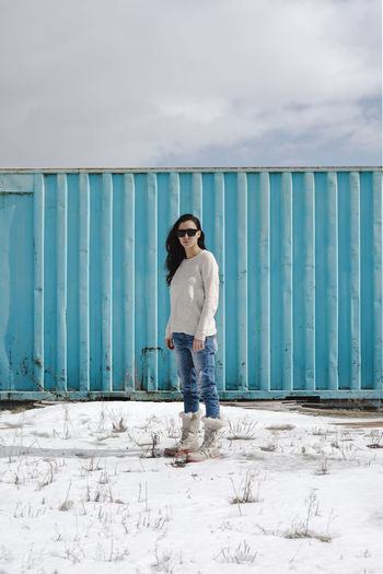 Portrait of woman standing against blue metallic container