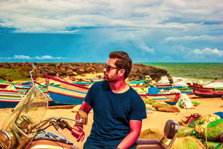 Indian man sitting on a motorbike at beach against sky