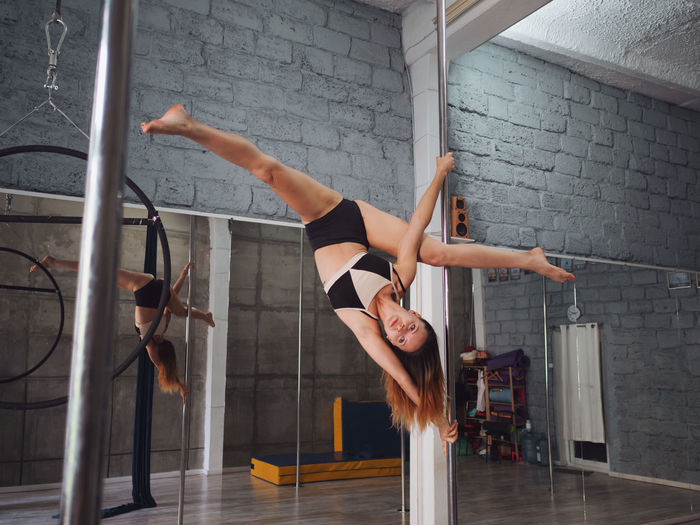 Full length of sensuous woman practicing pole dance reflecting on mirror in studio