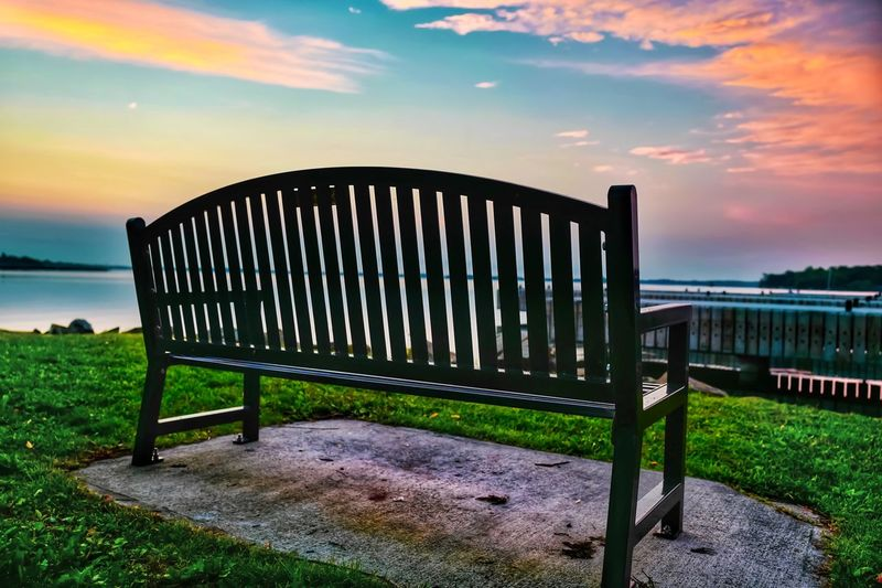 Beauty In Nature Shoreline Still Life Natural Beauty Sunrise And Clouds Sunrise Bench Chair Sky Cloud - Sky Nature Sunset Land Fence Field No People Grass Tranquil Scene Boundary Beauty In Nature Water Scenics - Nature Tranquility