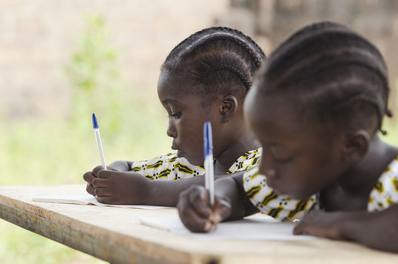 Close-up of girls writing in book