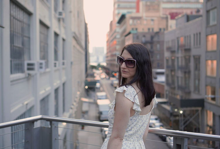 Portrait of woman wearing sunglasses while standing at balcony in city during sunset