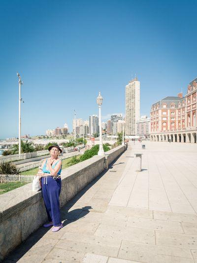 Full length of man on sidewalk in city against blue sky
