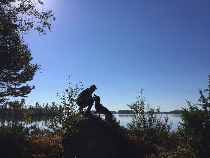 Low angle view of silhouette man jumping against clear sky