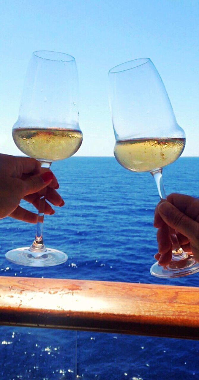 human hand, sea, human body part, drink, wineglass, food and drink, wine, alcohol, horizon over water, drinking glass, refreshment, outdoors, holding, beach, water, leisure activity, one person, sky, men, sunset, real people, day, close-up, clear sky, people, one man only, nature, adult, freshness, adults only, only men