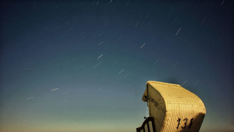 Scenic View Of Star Trails Over Hooded Beach Chair Against Sky At Night