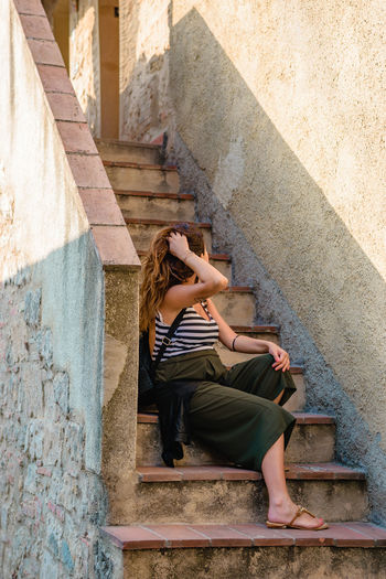 Woman sitting on staircase of house