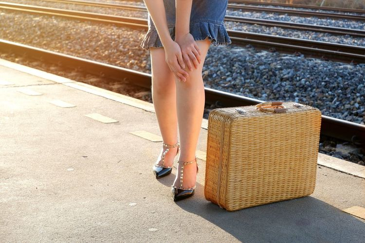 Low section of young female traveler massaging her knee in leg pain gesture and bamboo suitcase on railway platform with flare light on railroad tracks in train station Bamboo Suitcase Tourist Vintage Tone High-heeled Shoes Squeezing Female Young Lifestyle Journey Knees Leg Pain Traveler Travel Flare Light Pretty Leg Ache Railroad Tracks EyeEm Selects Low Section Women Human Leg Railroad Track Rail Transportation Train - Vehicle Limb Close-up Railroad Station Platform Railroad Station Railroad Platform Passenger Train
