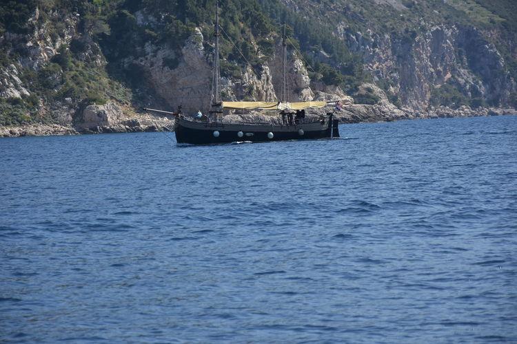 Boat sailing on sea against mountain