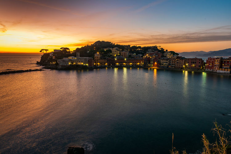 Scenic view of sea by townscape against sky during sunset