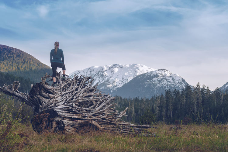 Rear view of woman standing on log at forest against cloudy sky