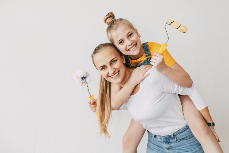 Beautiful and happy mom and daughter paint the walls in the apartment white