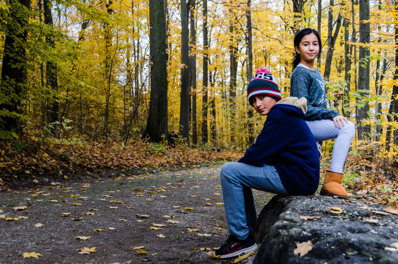 Portrait of smiling siblings on road in forest during autumn