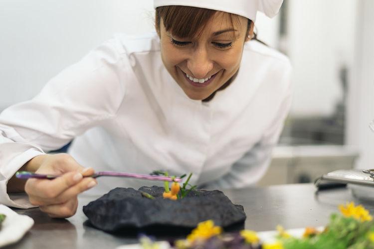Smiling woman garnishing food