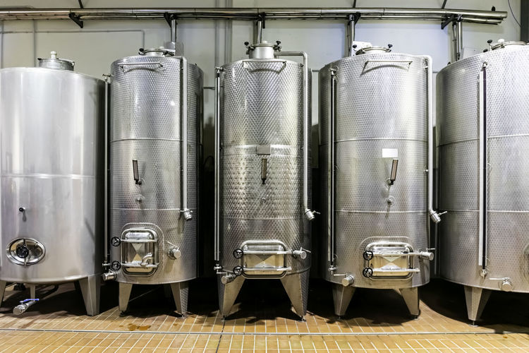 Metal silos for the fermentation of wine inside a farm. storage of wine in the cellar.