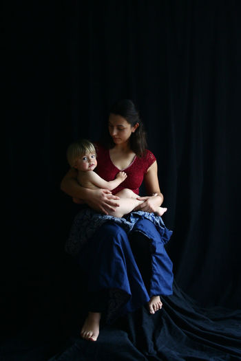 Full length of young woman with son sitting on black textile