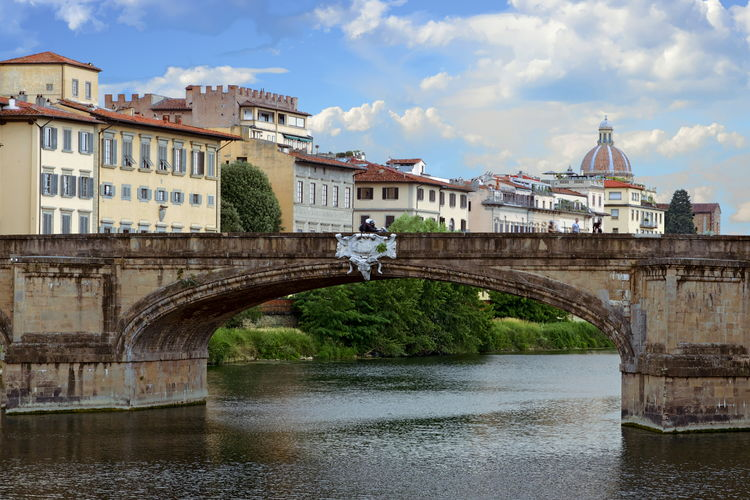 Arch Bridge Over River By Buildings Against Sky