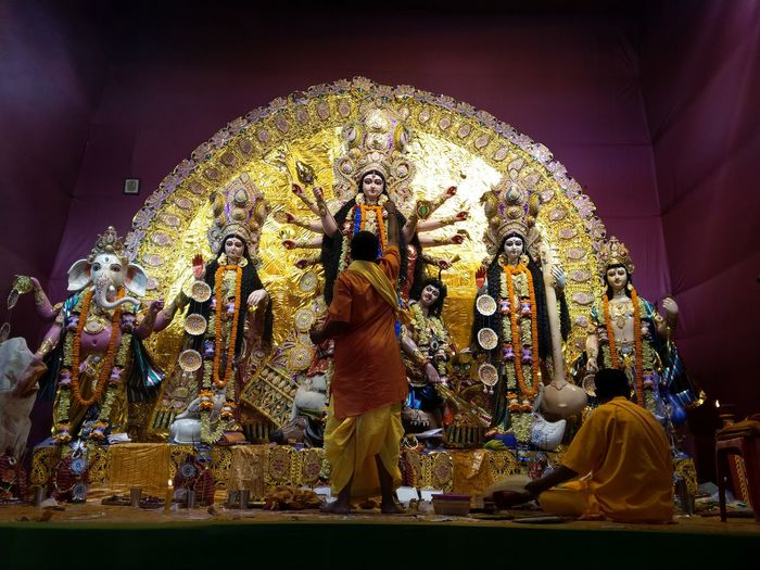 Rear view of priests worshiping goddess durga during festival