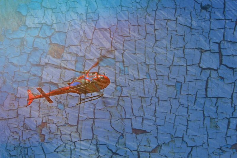 Low Angle View Of Red Helicopter Flying Against Patterned Wall On Sunny Day