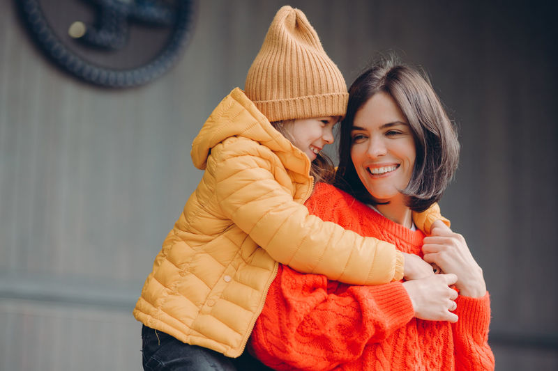 Cute girl with mother embracing outdoors