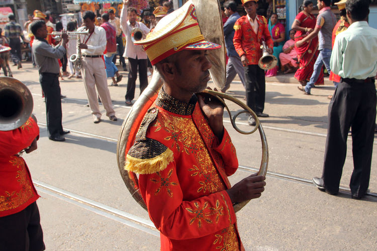 Side view of musician during procession at street
