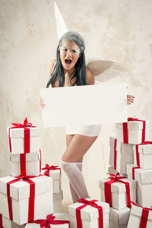 Beautiful young woman as angel with heap of gift boxes holding empty white board Celebration Christmas Event Holiday Looking At Camera Makeup Myth Presents White Board Woman Angel Angel Wings Brunette Caucasian Conceptual Empty Board Gift Boxes Gifts Indoors  One Person Red Ribbon Sexygirl Studio Shot Young Adult Young Women